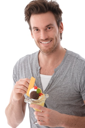 over eating: Portrait of handsome young man eating ice cream, smiling.