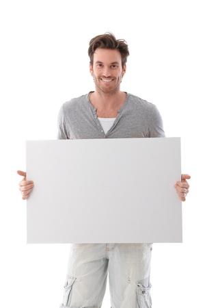 hoja en blanco: Goodlooking joven sosteniendo una hoja en blanco, sonriendo. Foto de archivo
