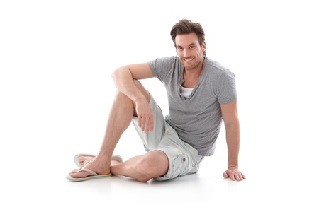 summer clothes: Handsome young man wearing summer clothes, sitting on floor, smiling.