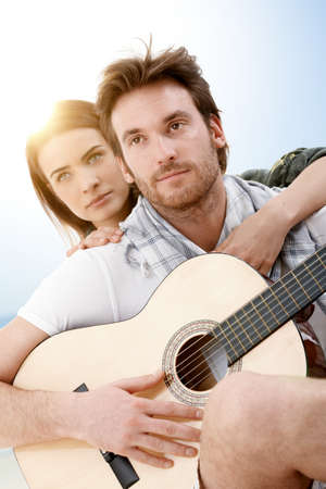 30s adult: Romantic young couple sitting on beach in summer sunlight embracing, playing guitar.