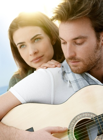 Romantic young couple embracing playing guitar outdoor in summer sunlight. Man in front in focus. photo