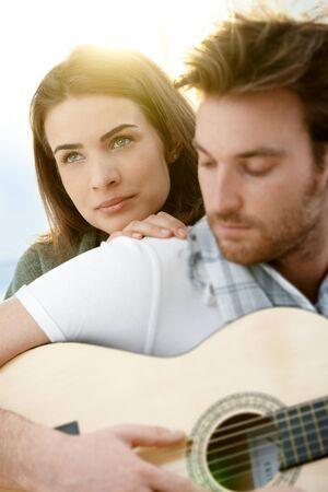 guitarra: Pareja joven rom�ntico abrazando a tocar la guitarra al aire libre en sol de verano. Mujer en foco. Foto de archivo
