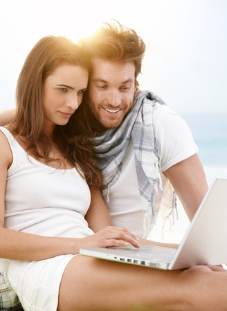 Attractive young couple sitting on the beach using laptop outdoor in summer sunlight, smiling. photo