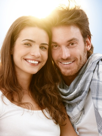 Portrait of happy young couple in summer sunlight, looking at camera, smiling. photo