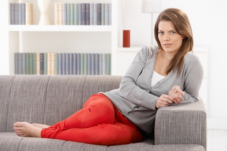 Pretty woman sitting on sofa in living room, smiling at camera, leisure, full length. Stock Photo - 9435342