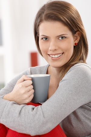 Cheerful woman sitting with coffee cup handheld, smiling happily at camera. Stock Photo - 9435288