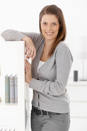 Pretty woman standing at book shelf at home, smiling happily at camera. photo