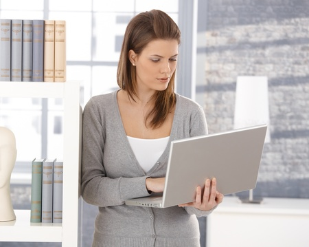 Pretty woman standing by bookshelf with laptop computer, typing. photo
