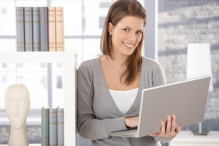 Happy woman standing at bookcase with laptop computer handheld, smiling at camera. photo