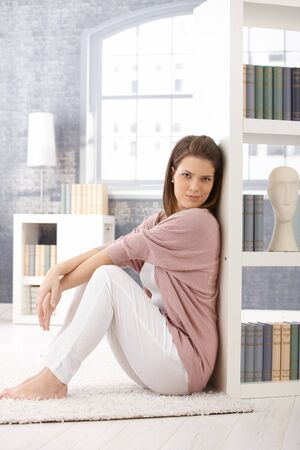 Attractive woman posing by bookcase, sitting on living room floor, smiling at camera. Stock Photo - 9435152