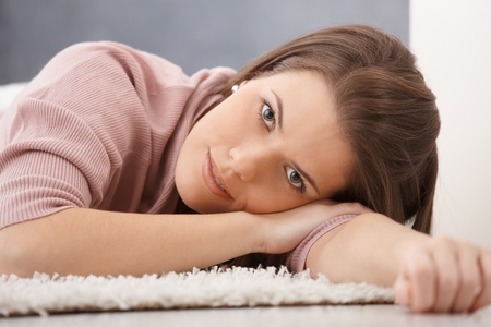 Daydreaming young woman lying on floor, smiling at camera. Stock Photo - 9435249
