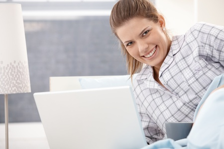 Happy woman wearing pyjama using laptop computer in bed, smiling at camera. photo