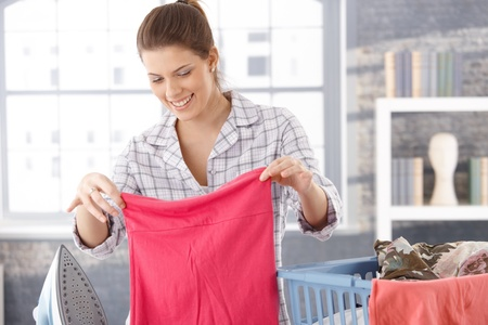 woman ironing: Happy woman doing laundry at home, holding clothes, smiling.