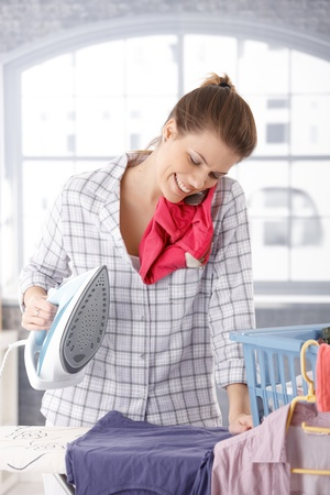 calling on phone: Happy woman talking on mobile phone while ironing clothes at home. Stock Photo
