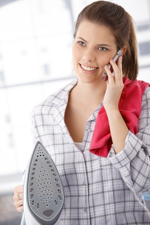Happy woman on phone call, doing ironing, holding iron and mobile phone. photo