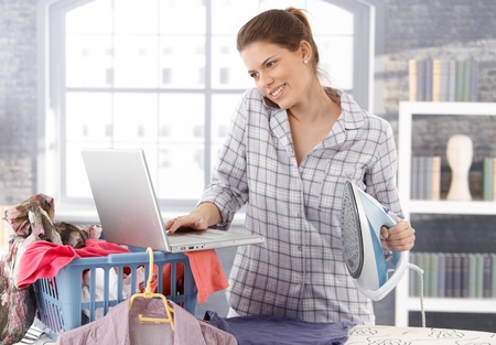 nighty: Multitasking woman at home, doing housework, ironing laundry and using laptop computer, talking on mobile phone, smiling. Stock Photo