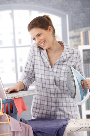 Laughing modern woman multitasking at home, using computer and cellphone, ironing clothes. photo