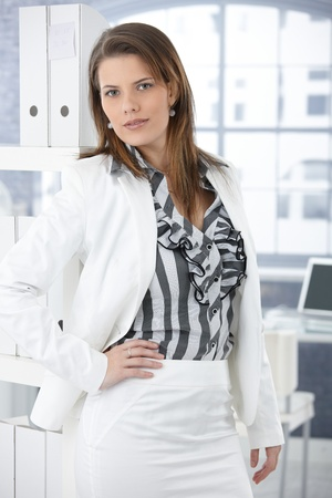 Trendy smart businesswoman posing in office, looking confidently at camera. photo