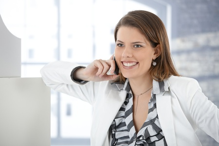 Cheerful businesswoman in elegant suit talking on mobile phone in office, smiling. Stock Photo - 9434926