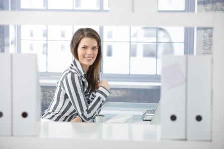 formal clothing: Pretty office worker sitting at desk in office, smiling at camera.