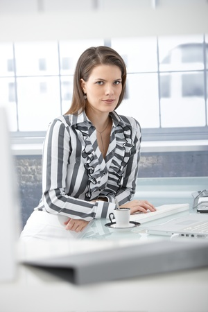 Businesswoman having coffee at desk, working on computer, smiling at camera. Stock Photo - 9435075