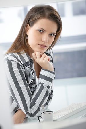 Businesswoman on coffee break, sitting at desk, smiling at camera confidently. Stock Photo - 9435283