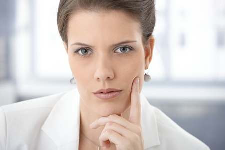 Closeup facial portrait of serious businesswoman thinking, looking at camera. photo