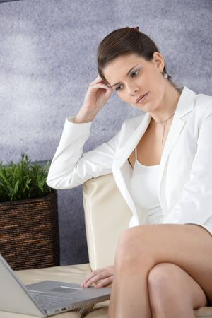 Attractive businesswoman in office lobby sitting on sofa, using laptop computer, thinking. photo