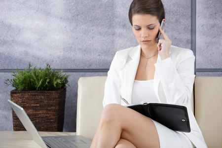 Smart businesswoman waiting in office lobby, busy working on mobile phone, using personal organizer. photo