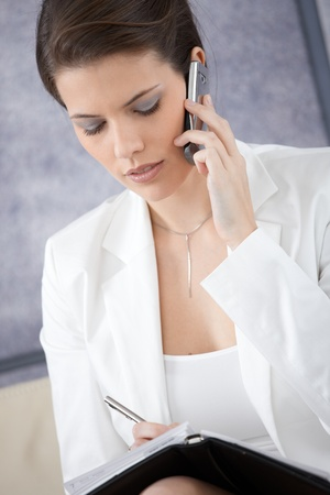 Businesswoman taking notes into personal organizer, concentrating on mobile phone call. photo