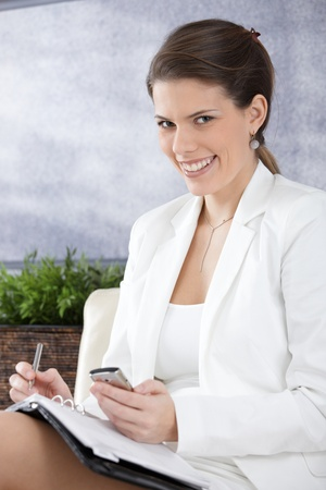 Happy businesswoman sitting in office lobby taking notes, using mobile phone, smiling at camera. Stock Photo - 9434899