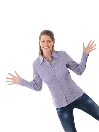 Happy attractive woman posing in studio with arms wide open, funny pose, smiling at camera. photo