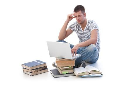 College student sitting among books, using laptop, studying. photo