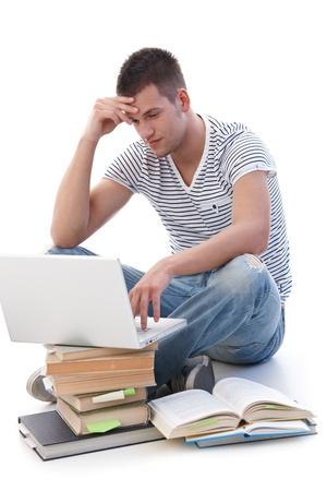 College student met behulp van laptop, zittend op de vloer, huiswerk maken.