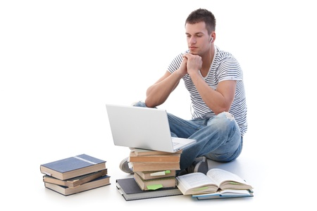 stubbly: Young college student using laptop, sitting among books, using headset.