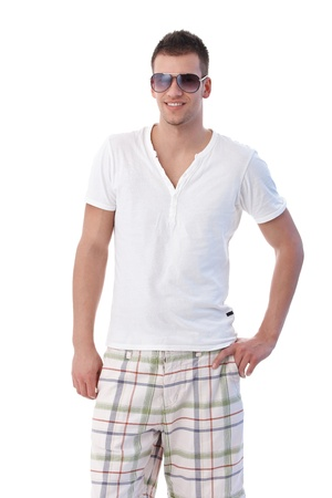 seasonal clothes: Handsome guy dressed for summer, wearing sunglasses, smiling. Stock Photo