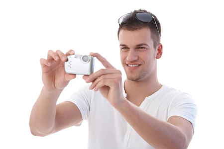 1 person: Young man in summertime using digital camera, smiling. Stock Photo
