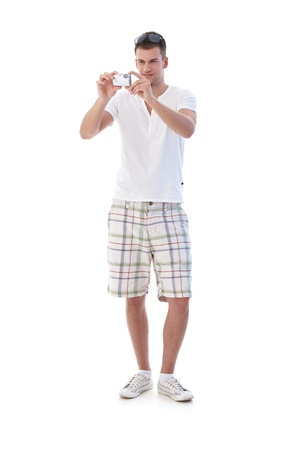 full face: Young man using digital camera in summertime, standing.