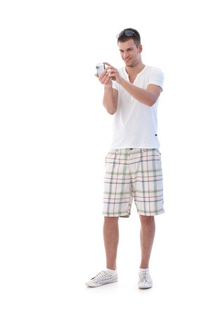 College student dressed for summer taking digital phot, smiling. photo