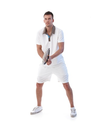 Young male tennis player waiting for ball, concentrating. photo
