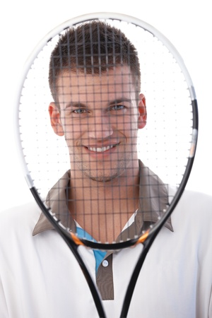 Young tennis player looking through tennis racket, smiling. photo