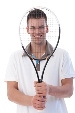 Young tennis player smiling happily holding tennis racket front of his face. photo