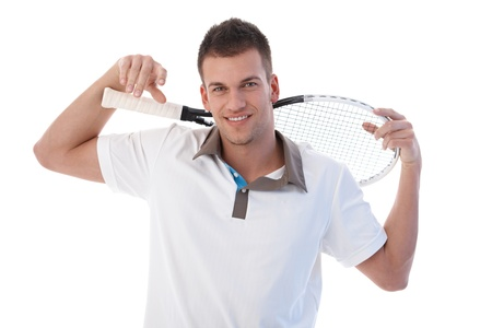 tennis racket: Young male tennis player taking a break, smiling, holding tennis racket.