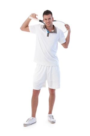 Handsome young tennis player posing with tennis racket in hand, smiling. photo