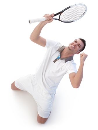 sport celebration: Young tennis player happy for victory, kneeling, looking up to the sky. Stock Photo