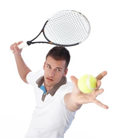 raqueta tenis: Apuesto joven tenista sirviendo, concentrando. Foto de archivo