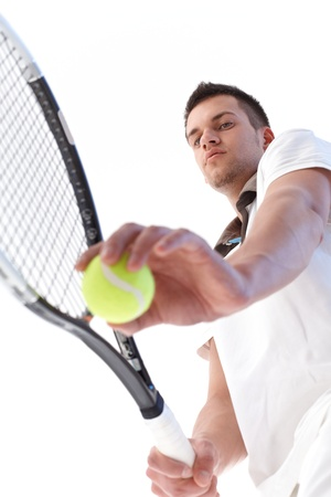 Young male tennis player preparing for serve, concentrating. photo