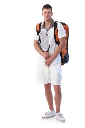 Handsome male tennis player going for training, holding tennis racket, smiling. photo