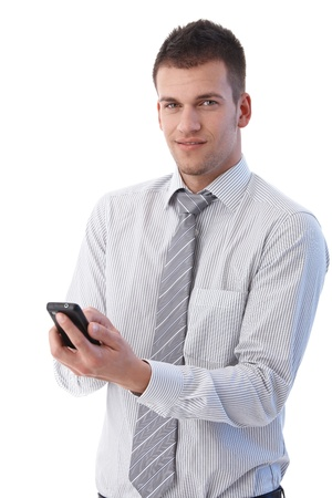 Handsome young businessman using mobile phone, writing text message, smiling. Stock Photo - 9538292