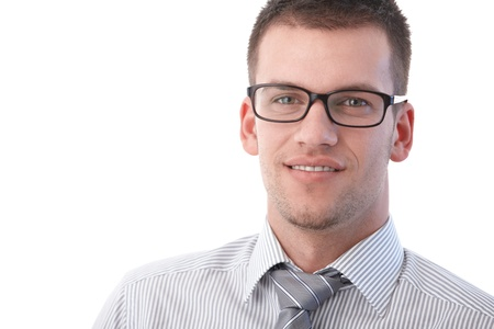 stubbly: Portrait of young businessman smiling, wearing glasses.